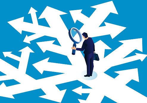 Businessman holding a magnifying glass standing in a complicated arrow path observing and making a choice