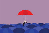 istock Businessman holding a red umbrella in the crowd of a blue umbrella 1193117289