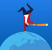 Businessman holding a telescope standing upside down on earth