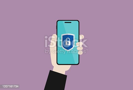 istock Businessman holds a mobile phone with a protective shield sign 1207161734