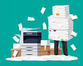 Businessman in pile of office papers and printer