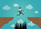 Businessman jump through the gap,business risk concept