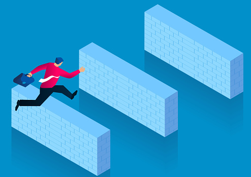 Businessman jumping over a series of brick wall obstacles, challenging the difficulties