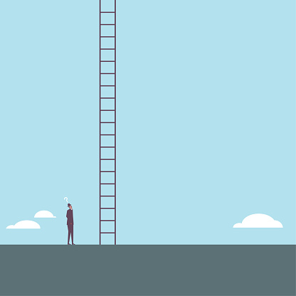 A businessman looked up at a ladder reaching into the sky.