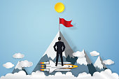 Businessman on the rocket launch and looking the red goal flag on peak mountain in the blue sky and clouds background as business, target, paper art and craft style concept. vector illustration.