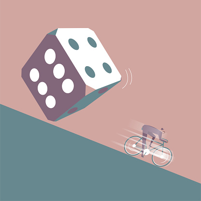 A businessman runs away on a bicycle in front of the huge dice.