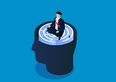 Businessman sitting cross-legged pensive on brain maze