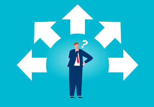 Businessman standing between surrounded by arrows thinking and choosing direction .