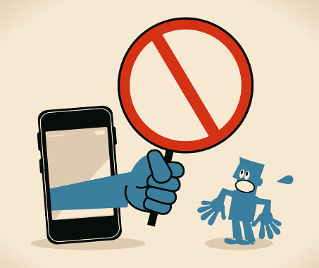 Businessman standing in front of a big smart phone, a big hand from the mobile phone holding an empty prohibition sign