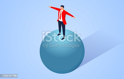 Businessman standing on huge ball trying to keep his body balanced