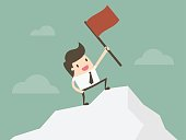 Businessman standing with red flag on mountain peak.