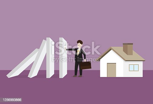 istock Businessman stops a domino effect to protect a house 1256993866