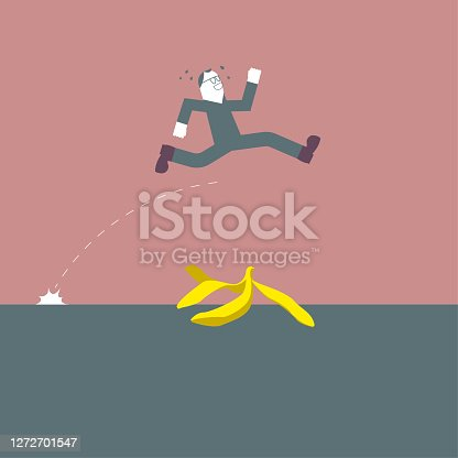 istock A businessman straddles banana peels,the background is brown. 1272701547