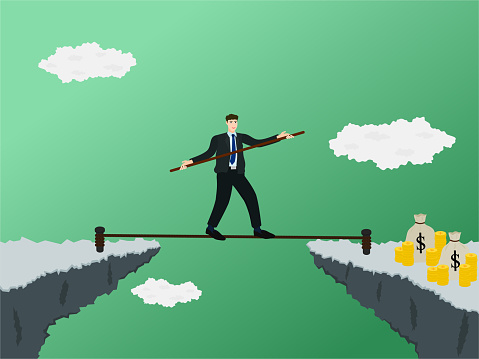 Businessman walking on rope across gap of cliff to profit money