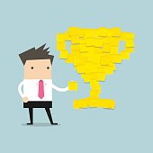 Businessman with trophy cup yellow sticky notes.