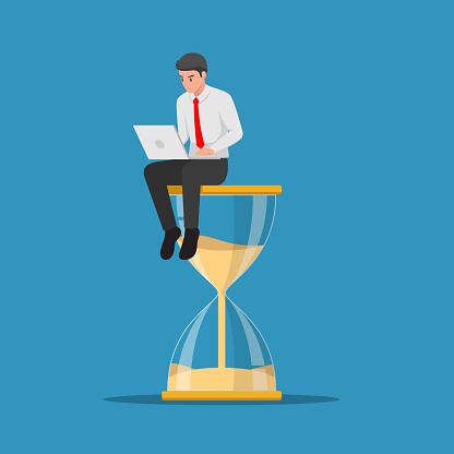 Businessman working with laptop sitting on big hourglass