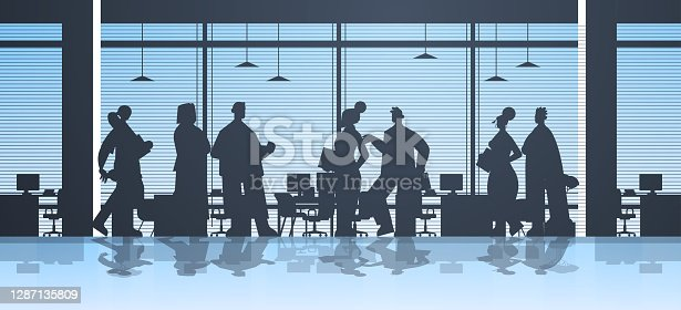 istock businesspeople silhouettes working in office business people group discussing during meeting teamwork concept 1287135809