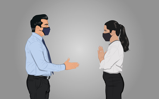 Businesswoman greeting businessman with namaste instead of handshake to prevent spreading of virus infectious disease