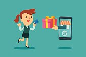 Happy businesswoman use credit card to shopping online and receive a gift box from smart phone. E-commerce concept.