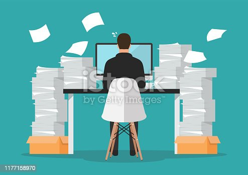 istock Busy businessman working on computer with pile of papers 1177158970