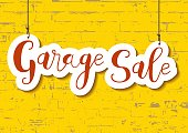 Calligraphy lettering of Garage sale in orange in paper cut style on yellow textured brick wall background for advertising, invitation, banner, poster, flyer, handbill