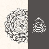 Calligraphy of text Eid Mubarak with stylish floral design.