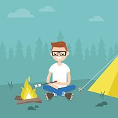 Camping in forest. Young character roasting marshmallows on fire / flat editable vector illustration, clip art