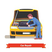 Car mechanic repairs engine at car service station