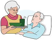 Elderly woman bringing meal to sickly older man in bed