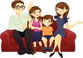 A family consisting of a father, mother, a teenage daughter, and a little son sitting on a sofa.