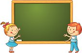 Little kids at the blackboard in the classroom, frame with a copy space