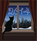 Cat in Silhouette Watching Snowy City from Window.