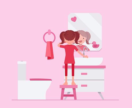 Child girl keeps teeth clean by brushing in bathroom
