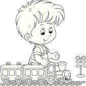Little boy playing with a small toy train