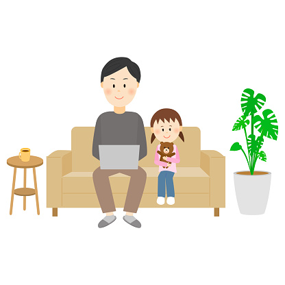 A child watching with his father working on the couch at home