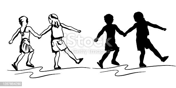 Two children walking while holding hands