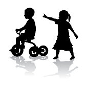 Toddler girl pointing towards a little boy on his tricycle