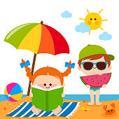 Children at the beach reading a book and eating a slice of watermelon under a beach umbrella