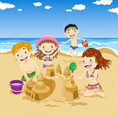 Four children building sand castle in the summer.