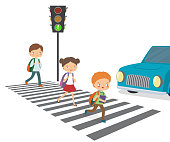 Children cross the road to a green traffic light