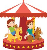 Children have fun in amusement park and ride on carousel
