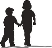 Silhouette of two children, a boy and a girl, walking hand in hand