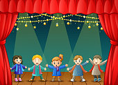 Children in winter clothes performing on stage