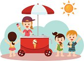a group of cute kids buying ice cream on the beach.