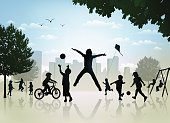 Silhouette of children playing in the city park.