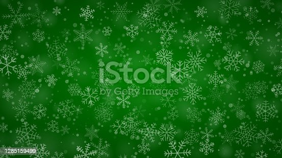 Christmas background of snowflakes of different shapes, sizes and transparency in green colors