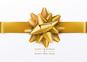Christmas background. White gift box with golden bow and horizontal ribbon