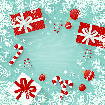 Christmas background with decorations and gift boxes, white fir tree branches on wooden table