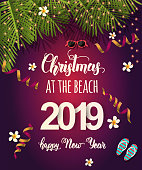 "Christmas background with palm leaves, light bulbs, sunglasses, tropical flowers, serpentine and hand written quote ""Christmas at the beach. Happy New Year 2019"". Banner,poster, flyer, brochure"