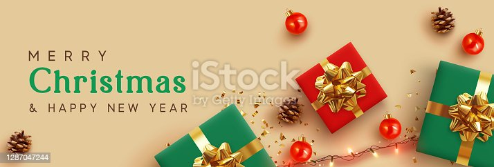 istock Christmas banner. Background Xmas design of realistic red and green gifts box, golden glitter confetti, bauble ball, light garlands. Horizontal New Year poster, greeting card, headers for website 1287047244